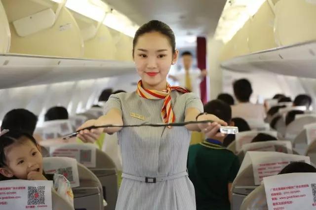 在飞机客舱内,乘务员拿出安全带